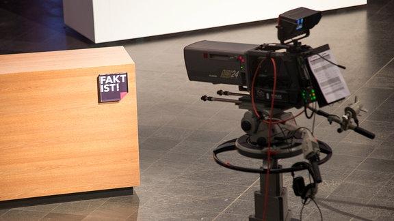 """Eine Kamera steht vor einem rechteckigen, halbhohen Podest aus hellem Holz. An einer Ecke des Podests ist ein quadratisches Logo mit der Aufschrift """"Fakt ist"""" abgebildet."""