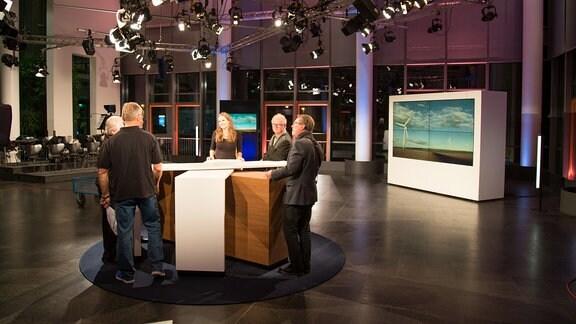 In einem Fernsehstudio stehen eine Frau und fünf Männer im Kreis um einen Tisch.