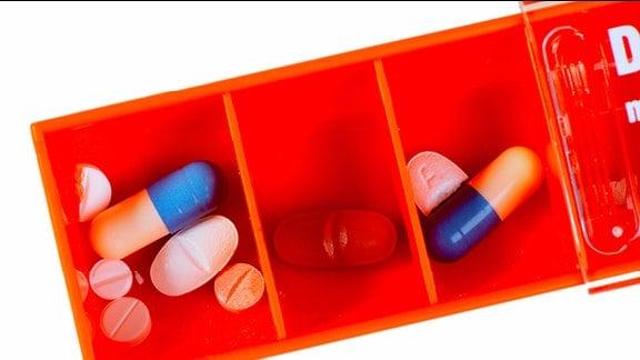 Verschiedene Tabletten in den Fächern einer Tablettenbox.