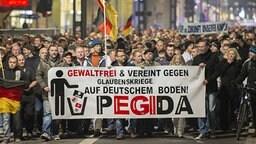 Teilnehmer einer Demonstration des Bündnisses Patriotischer Europäer gegen Islamisierung des Abendlandes (Pegida) laufen durch die Dresdner Innenstadt. | imago/Robert Michael