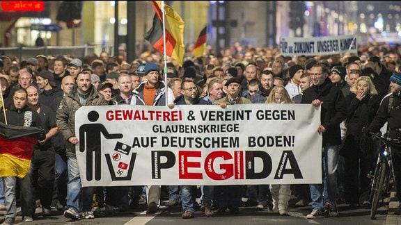 Teilnehmer einer Demonstration des Bündnisses Patriotischer Europäer gegen Islamisierung des Abendlandes (Pegida) laufen durch die Dresdner Innenstadt.
