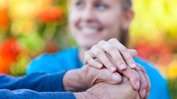 Die Hände eines Senioren halten einen Gehstock. Eine junge Frau stützt ihn.