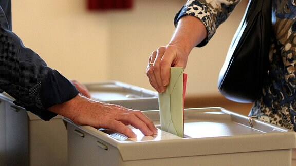 Wählerin wirft Wahlumschlag in eine Wahlurne.