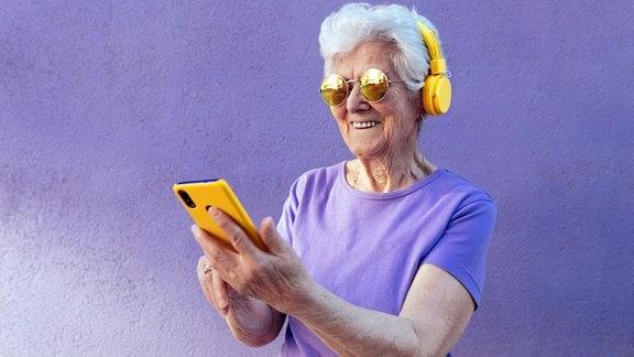 Fesche Oma mit Kopfhöhrern und Smartphone
