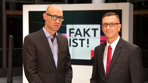 """Zwei Männer (Reporter Lars Sänger li. und Moderator Dr. Andreas Menzel re.)  in Anzügen stehen vor einer Wand mit dem Logo der Fernsehsendung """"Fakt ist"""""""