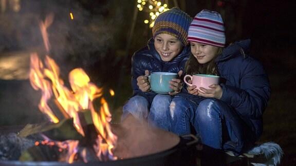 Junge und Mädchen sitzen mit Bechern in den Händen an einem Feuer.