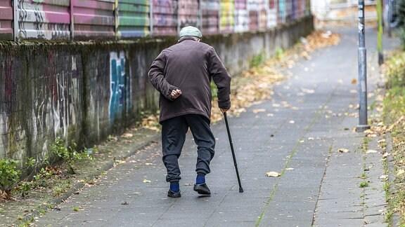 Alter Mann geht langsam, auf einen Gehtstock gestützt