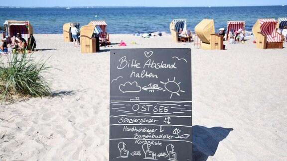 Ein Schild mit der Aufschrift 'Bitte Abstand halten' steht am Zugang zum Strand an der Ostsee.