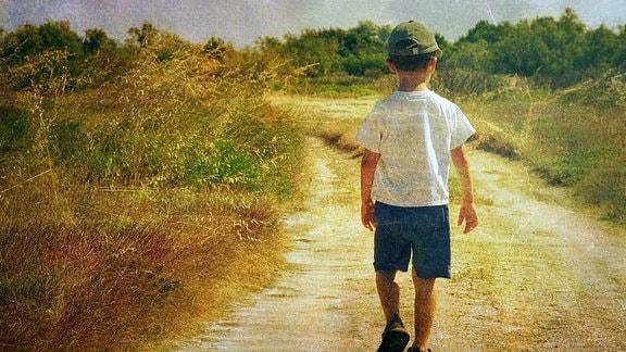 Kind läuft allein auf einem Feldweg.