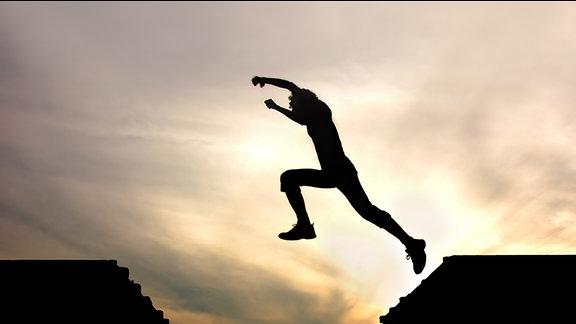 eine Frau springt über einen Graben