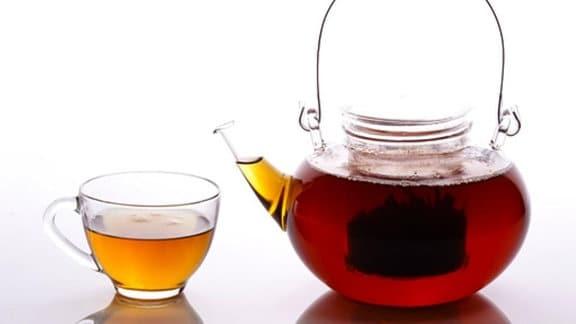 Eine gläserne Teekanne ist gefüllt mit rotem Tee. Neben dieser steht ein Teetasse aus Glas, welche ebenfalls mit Tee gefüllt ist.