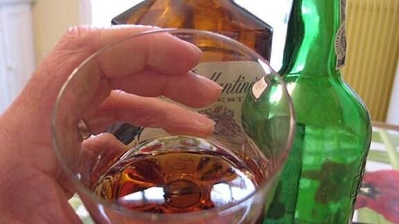 Ein mit einer braunen Flüssigkeit gefülltes Glas und 2 leere Schnapsflaschen.