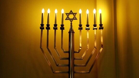Ein in der Mitte mit einem Davidstern verzierter achtarmiger Leuchter mit brennenden Lampen