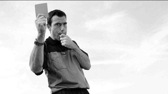 Ein Schiedsrichter zeigt eine Karte