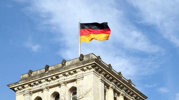 Die Flagge der BRD weht auf dem Reichstag in Berlin.