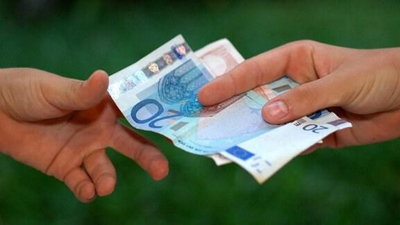 Zwei Hände mit wechselndem Geldschein.