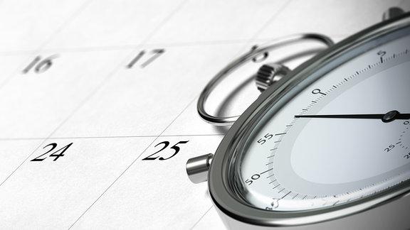 Eine gelbe Stoppuhr liegt auf einem kalender