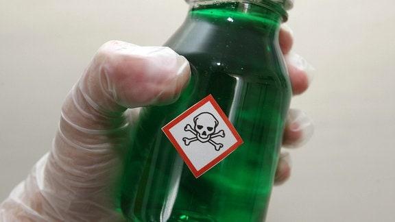 Ein Fläschlein, welches eine grüne Flüssigkeit enthält und mit einem Aufkleber eines Totenkopfes versehen wurde.