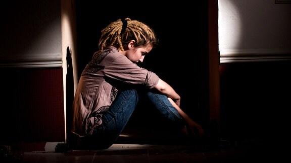 Teenager sitzt in einem abgedunkelten Raum