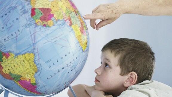 Kind schaut auf einen Globus