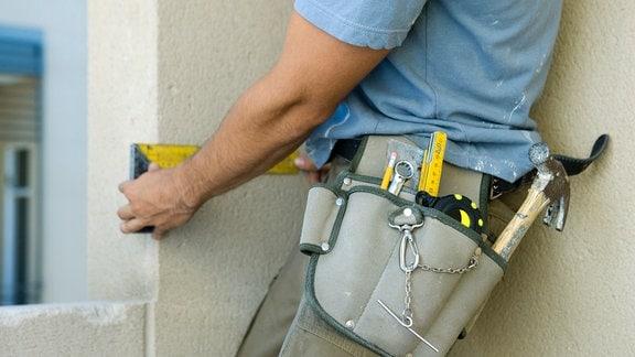 Handwerker mit Werkzeuggürtel legt einen Messwinkel an eine Fensterleibung an