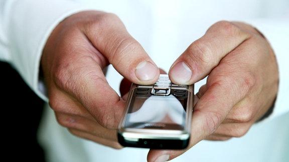 Ein Mobiltelefon wird von zwei Händen gehalten und mit den Daumen auf der Tastatur zwecks SMS-Eingabe  getippt