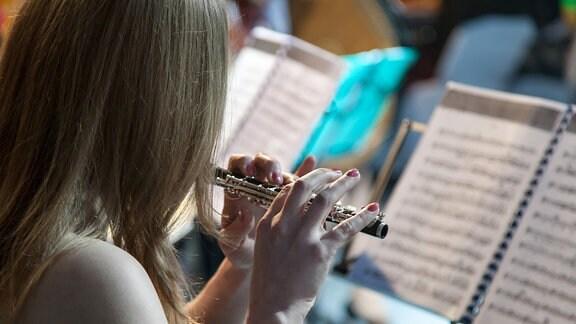 Ein Flötist im Orchester von hinten
