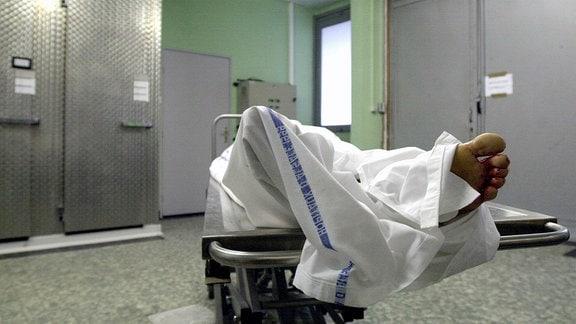 eine mit einem Tuch bedeckte Leiche im Leichenschauhaus