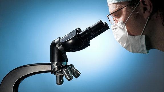 Wissenschaftler mit Mundschutz schaut durch ein Mikroksop