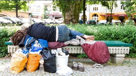 Obdachloser schläft auf Parkbank