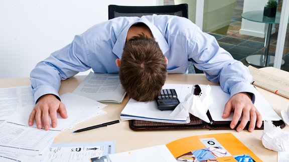Ein Mann im Büro mit dem Kopf auf dem Tisch.