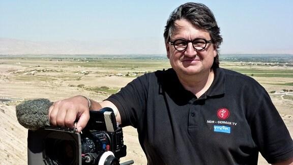 Thomas Junker steht neben seiner Kamera und schaut lächelnd. Im Hintergrund eine weite Steppenlandschaft mit einigen Siedlungen.
