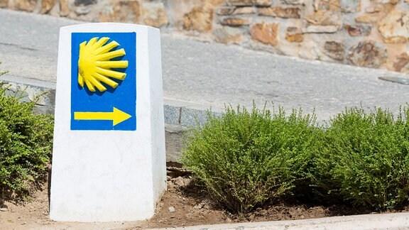 Steinerner Wegweiser auf dem Jakobsweg mit Muschelsymbol