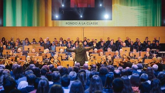 Blick über die Zuschauer auf den Dirigent und das Orchester.