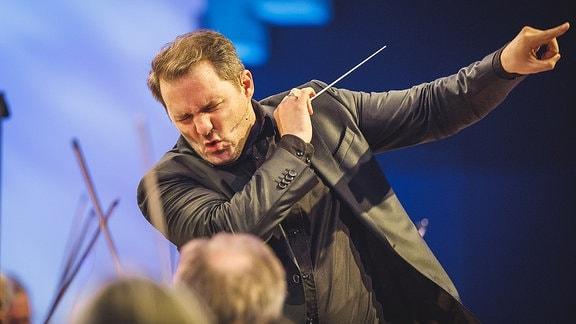 Der Dirigent gibt dem Orchester Anweisungen.
