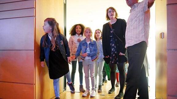 Kinder betreten Konzertsaal in Begleitung von zwei Erwachsenen.