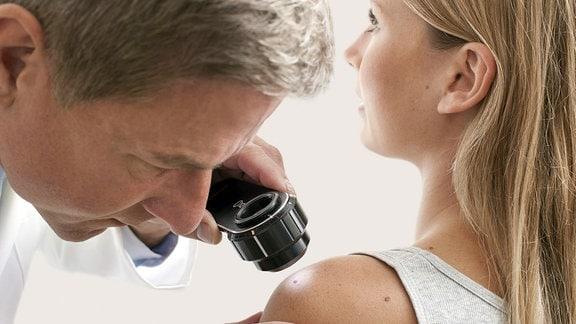 Hautarzt untersucht eine Frau