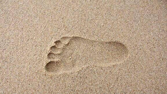 Ein Fußabdruck im Sand.