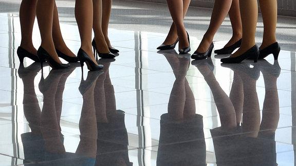 Beine von Flugbegleiterinnen auf einem spiegelnden Fußboden.