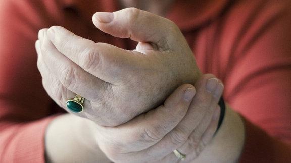 Eine alte Frau hält sich ihre schmerzendes Handgelenk.