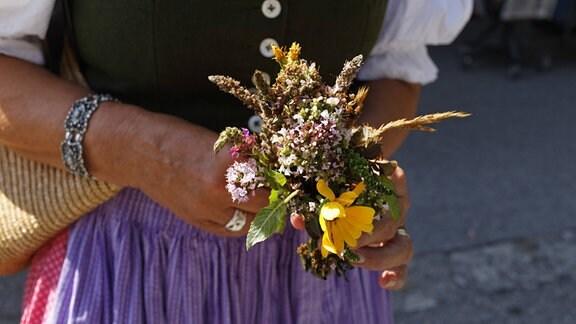 Eine Frau hält einen sogenannten Kräuterbuschen, einen Straß aus verschiedenen Sommerkräutern, in der Hand