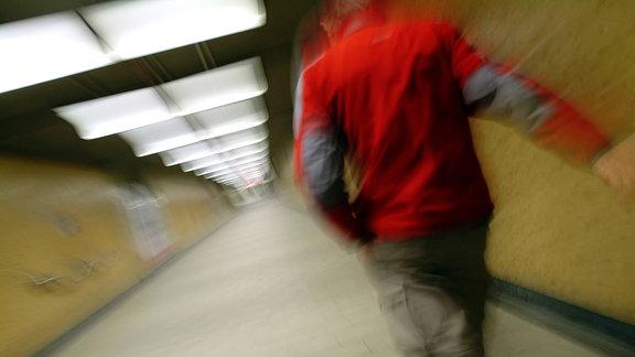 Bewegungsunscharfe Aufnahme eines Mannes, der durch eine Unterführung geht.