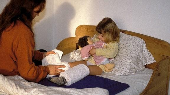 Eine Mutter legt ihrer kleinen Tochter Wadenwickel um