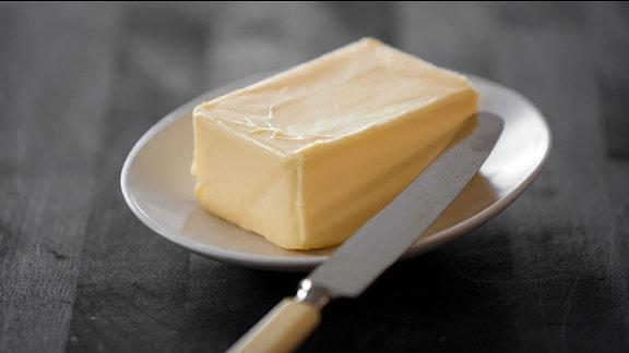 Ein Stück Butter liegt neben einem Messer auf einem Teller