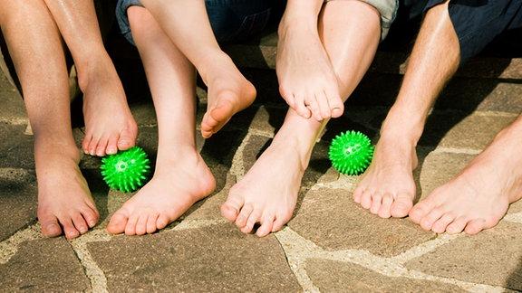 Nackte Beine und Füße mehrerer Personen, dazwischen liegen Igelbälle