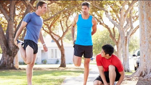 Drei Männer machen Dehnungsübungen vorm Joggen.