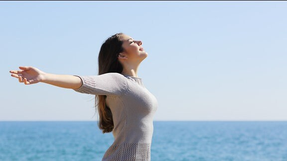 Eine junge Frau steht am Strand und breitet die Arme aus