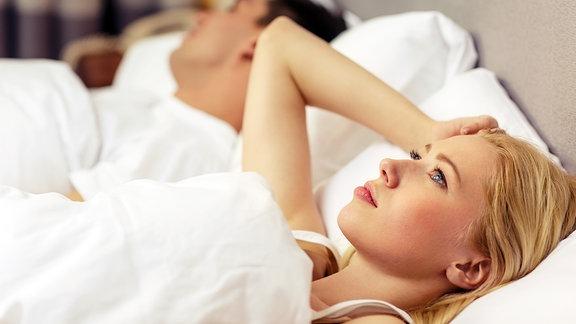 Eine Frau liegt im Bett neben ihrem schlafenden Partner