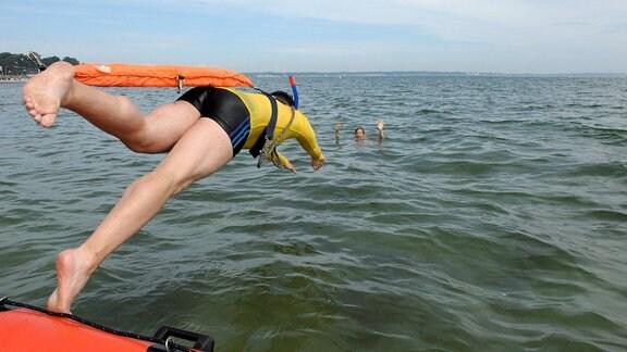 Ein Rettungsschwimmer springt von einem Boot aus ins Wasser