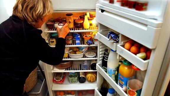 Einen Frau holt einen Joghurtbecher aus einem gut gefüllten Kühlschrank